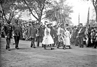 African American Civil War veterans wearing G.A.R. caps and uniforms and young women marching in procession, May 30, 1912