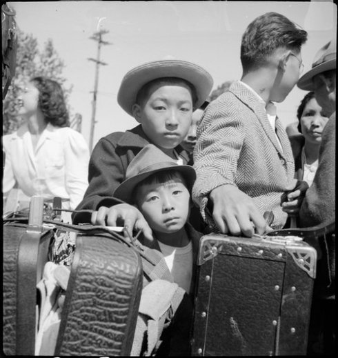 Turlock, California. These young evacuees of Japanese ancestry are awaiting their turn for baggage . . .
